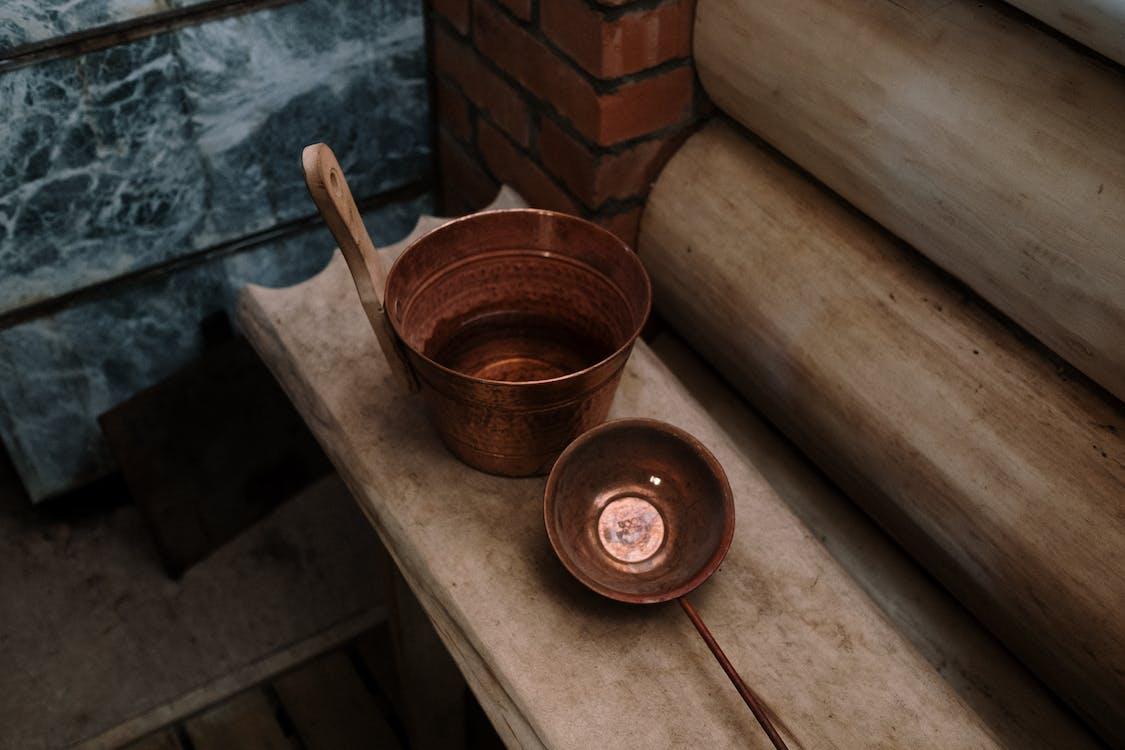 Brown Wooden Ladle in Brown Round Plastic Bucket