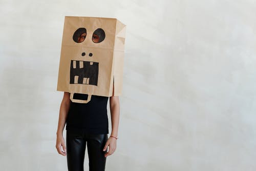 A Kid Wearing A Funny Face Drawn On A Paper Bag