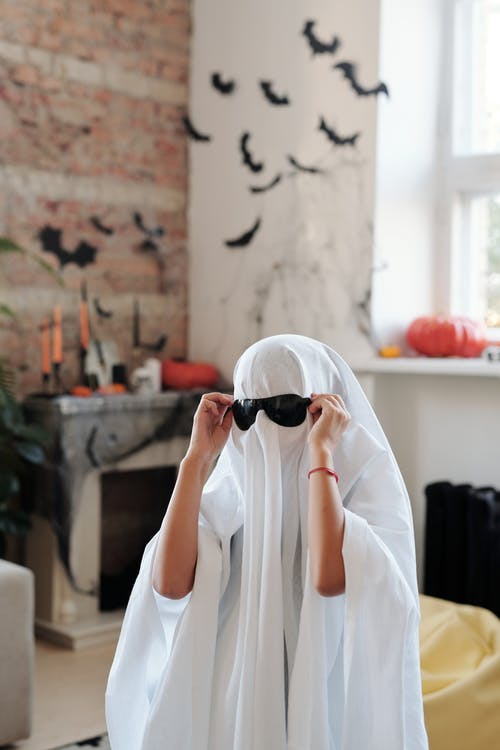 A Kid In A Ghost Costume