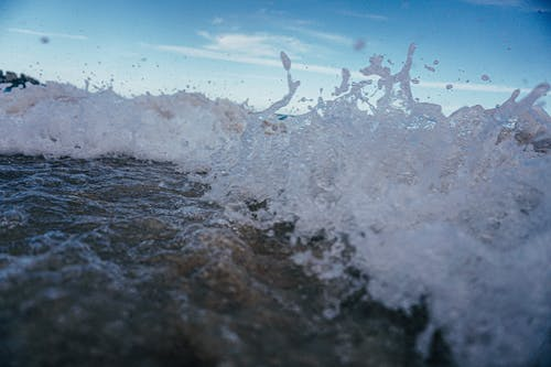 Crystal transparent foaming water of splashing waves rolling on sandy beach in resort