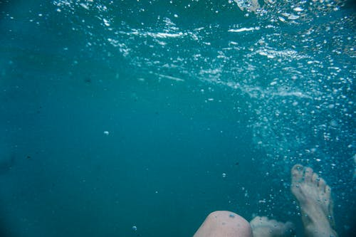 Person drowning in clean blue water
