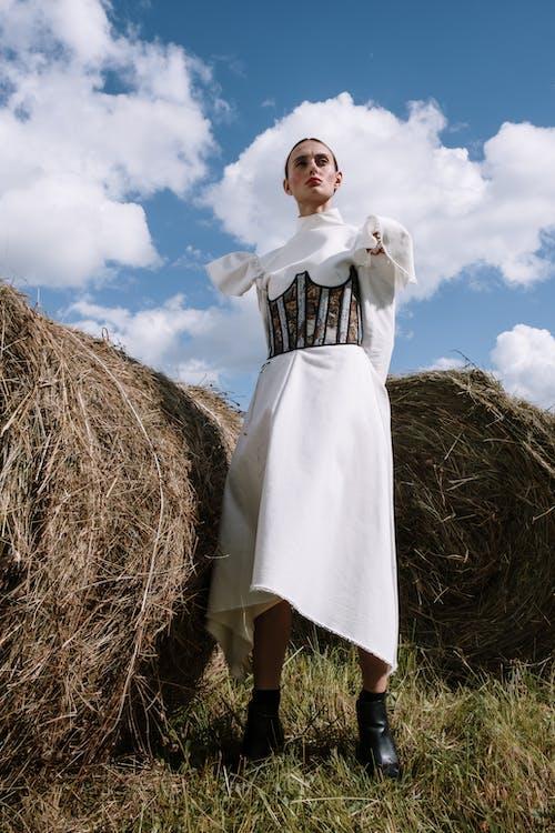 Woman in White Dress Standing Beside Haystack