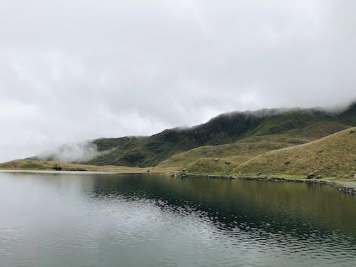 Green Mountain Beside Body of Water Under White Sky