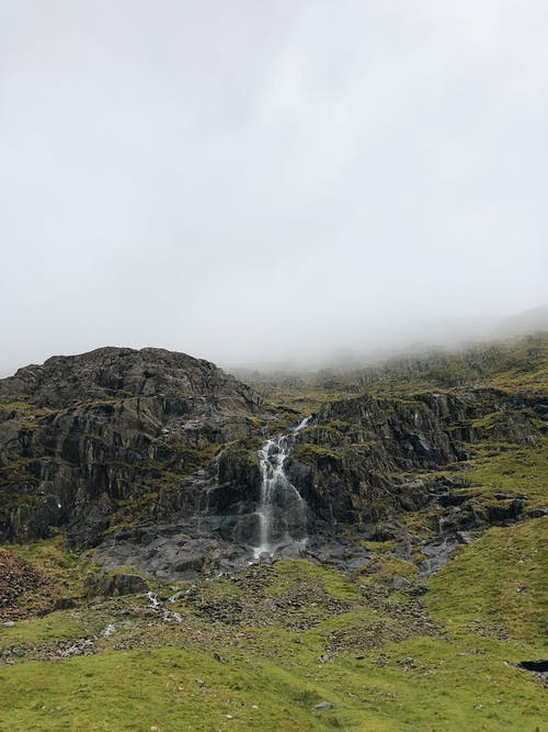 Waterfalls on Brown Rocky Mountain Under White Cloudy Sky
