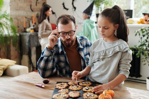A Girl Decorating Cookies With Her Father