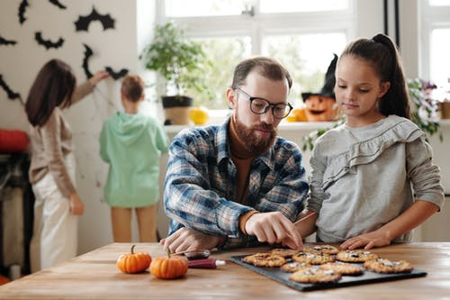 Father And Daughter Checking On The Halloween Cookies