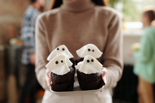 Woman Holding Chocolate Cupcakes On A Tray