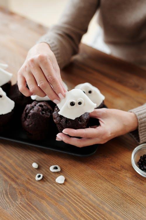 Person, Die Einen Schokoladen Cupcake Verziert