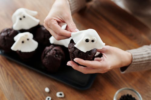 Person Holding Chocolate Cupcake With White Icing on Top