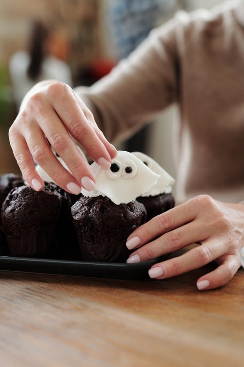 Person Holding Chocolate Cupcake With White Icing on Black Plate