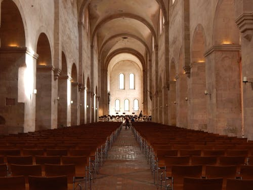 Perspective of walkway with rows of seats in cathedral aisle with stone columns and ceiling