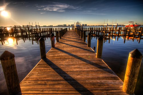 Brown Wooden Dock on Blue Water Under White Clouds and Blue Sky during Daytime