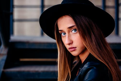 Stylish young lady in modern hat on street