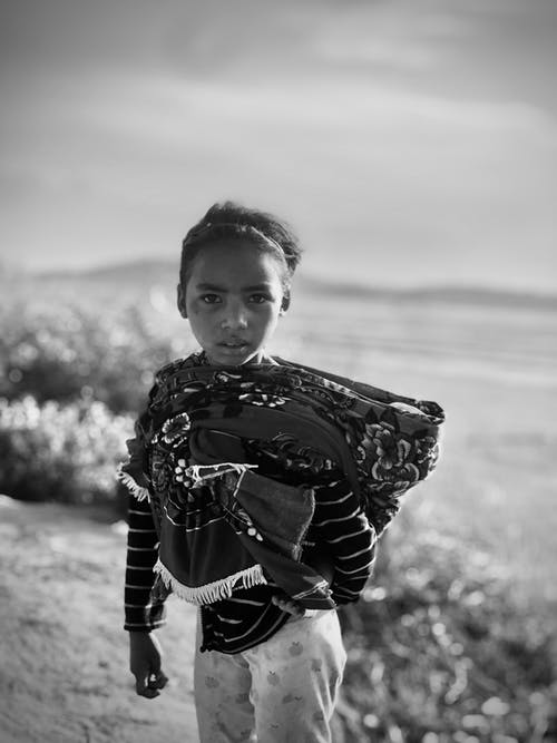 Grayscale Photo of Child Looking at the Camera
