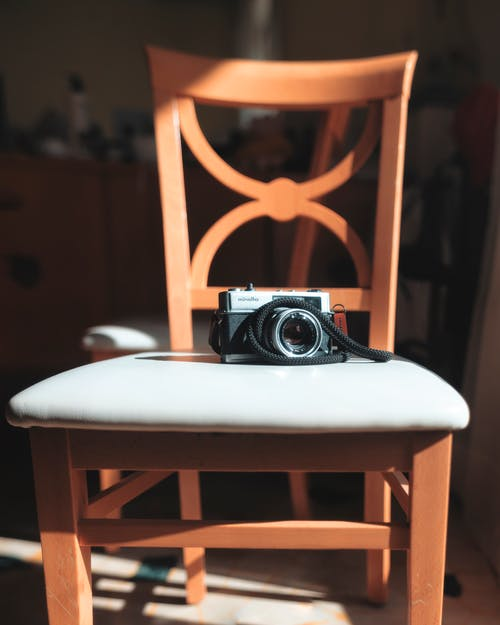 Black and Silver Dslr Camera on White Wooden Chair