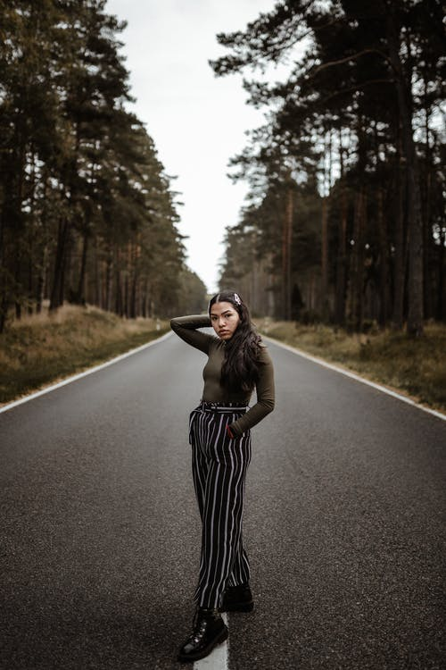 Woman in Black and White Striped Dress Standing on Road