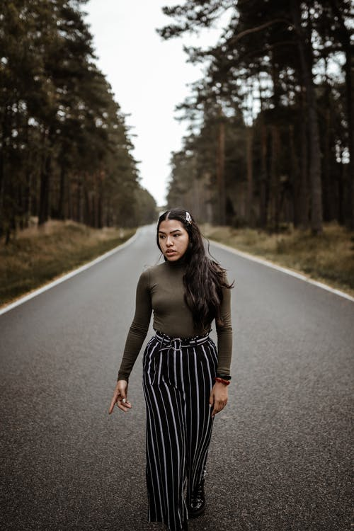 Woman in Brown Long Sleeve Shirt and Black and White Striped Skirt Standing on Road during