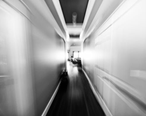 Black and white empty narrow hall between white walls leading to living room of contemporary house