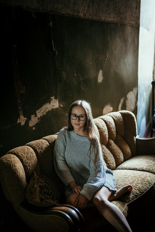Woman in Gray Sweater Sitting on Brown Couch