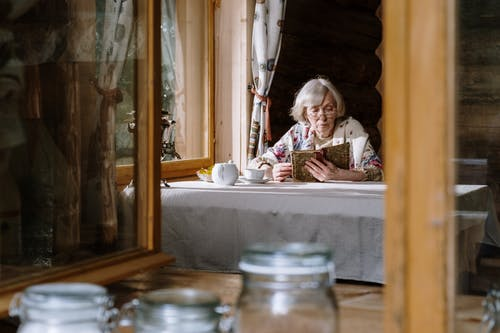 Elderly Woman Reading on the Table