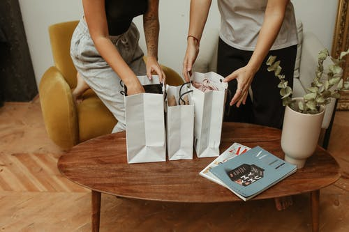 Hand of Woman in Gray Pants Inside White Paper Bag