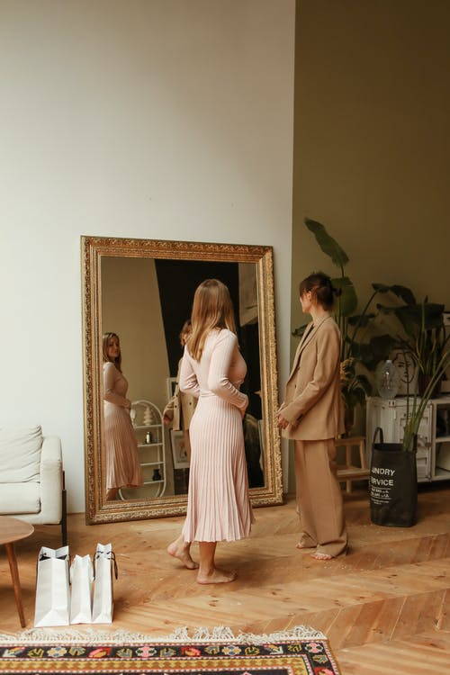 Women Fitting Clothes in Front of a Mirror