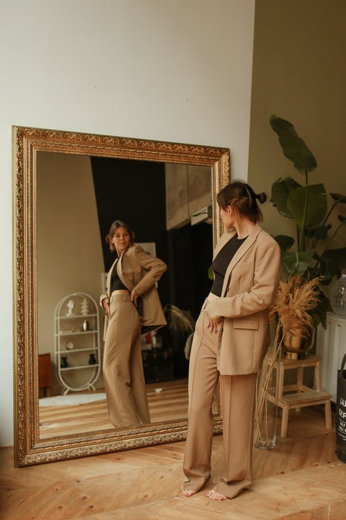 Woman Fitting a Brown Coat in Front of a Mirror