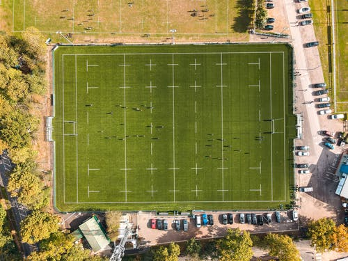 Aerial view of unrecognizable people playing rugby on well groomed green field on sunny day in countryside