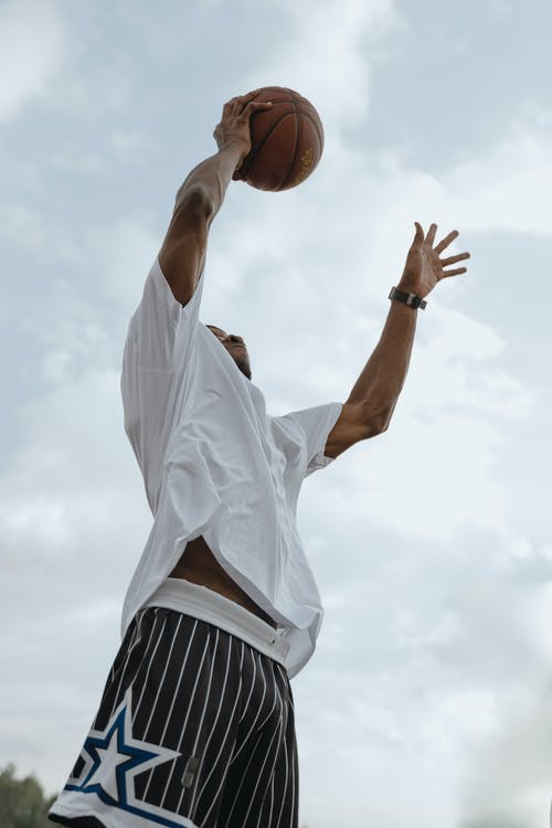 Man in White Shirt and Black Shorts Holding Basketball