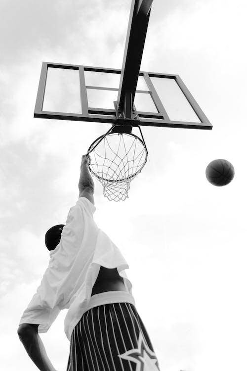 Man in White Shirt Playing Basketball