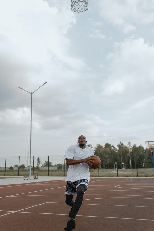 Man in White Shirt and Brown Shorts Playing Basketball
