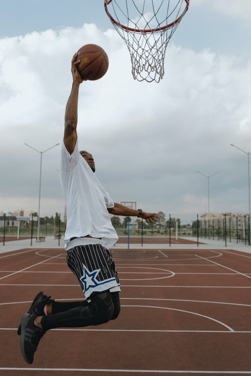 Man in White T-shirt and Black and White Shorts Playing Basketball