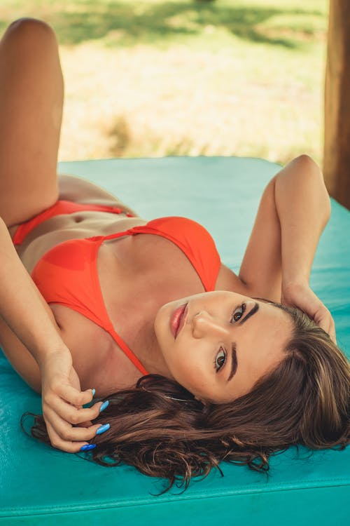 Young sensual woman in bright swimwear with manicure and makeup touching hair while lying on bed and looking at camera