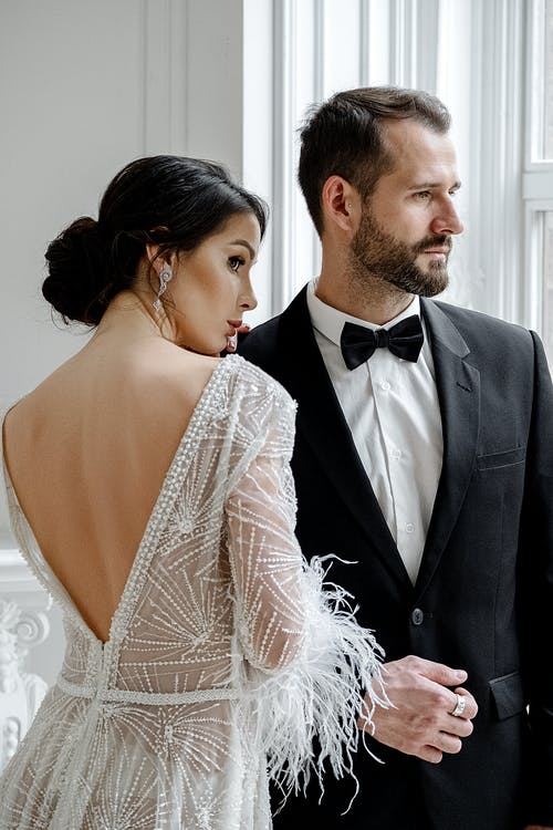 Young elegant newlywed couple wearing fancy wedding gowns standing close in light spacious studio and looking away