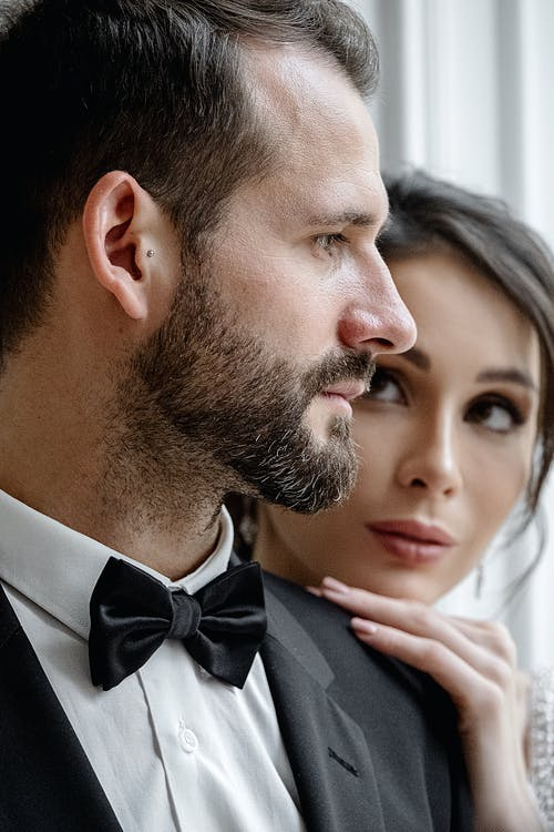 Crop gorgeous bride touching grooms shoulder gently and looking at content handsome groom face during wedding photo session in light studio