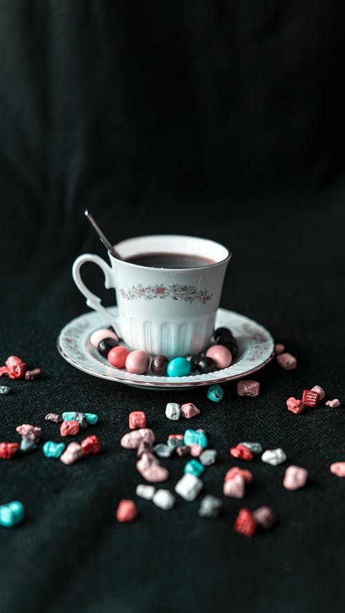 From above of aromatic coffee in porcelain cup with spoon and bright sweets on saucer and table