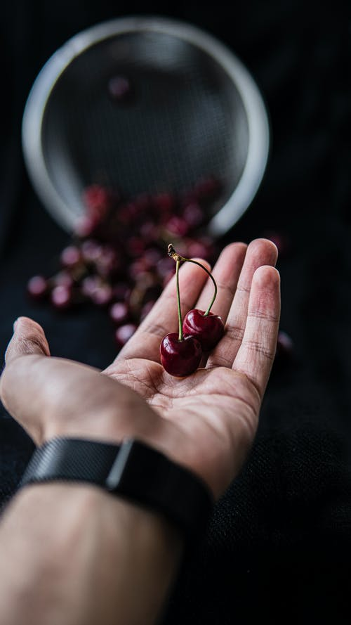 Crop man showing tasty ripe cherries on blurred background