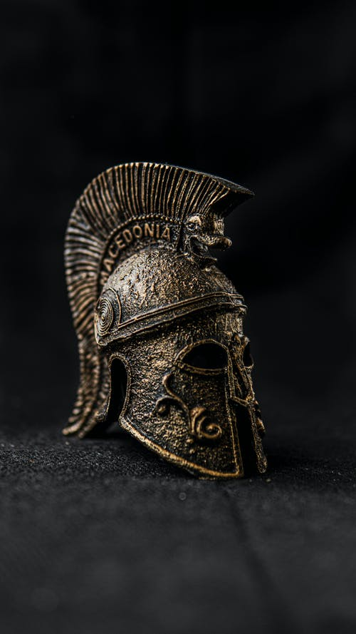Ancient Greek helmet made of bronze with decorative elements in museum in darkness