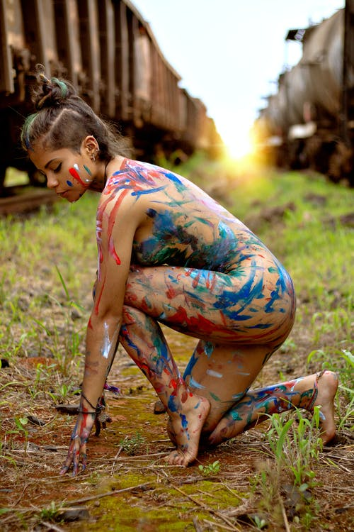 Nude woman covered with paint sitting between trains