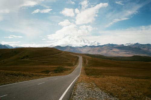Wavy road in high mounts under blue cloudy sky