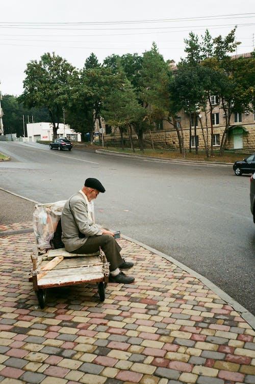 Unrecognizable senior man resting on old garden cart near road