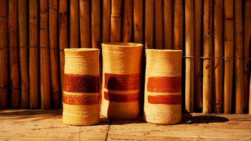 Similar clay jugs with ornament near bamboo fence