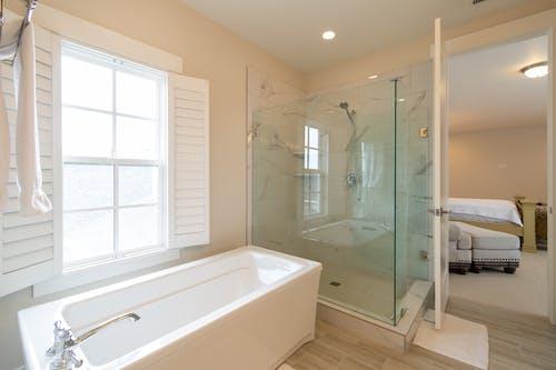 White Bathtub Near White Window Blinds