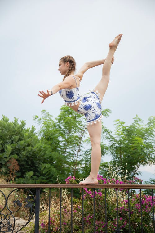 Flexible ballerina standing with raised leg on fence