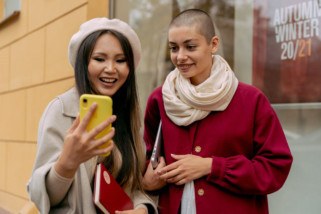 Woman in Red Coat Holding Yellow Smartphone