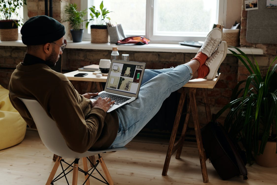 Man in Brown Sweater Reading Newspaper