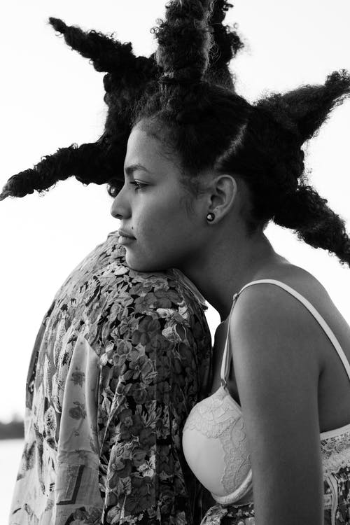Black and white side view of peaceful African American couple standing close to each other and hugging