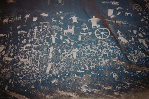 Newspaper rock with ancient symbols and petroglyphs with white paint on shabby stone blue wall with uneven surface in national park