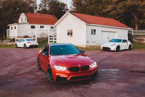 Stylish cars parked near old cottages in countryside