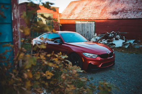 Trendy red coupe car parked near abandoned barns in countryside